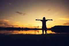 Young woman standing and hand up on sunset stock image