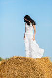 Young woman standing on a hay bale Royalty Free Stock Image