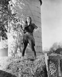 Young woman standing on a haystack and holding a pitchfork Royalty Free Stock Image