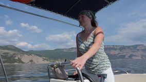 Young woman standing at the helm of the motorboat. Sea stock video