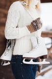 Young woman standing with her ice skates slung over her shoulder Royalty Free Stock Image