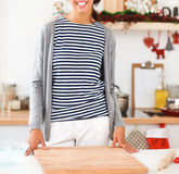 Young woman standing in her kitchen near desk Stock Images