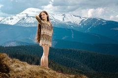 Young woman standing on a hillside in the mountains Royalty Free Stock Photos