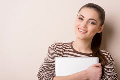 Young woman standing and holding laptop. Stock Photos