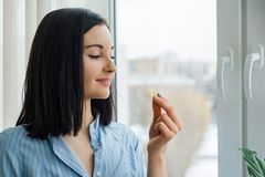 Young woman standing at home near the window taking vitamin Omega 3 fish oil yellow capsule royalty free stock photo