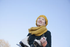 Young Woman Standing with Ice Skates Royalty Free Stock Images