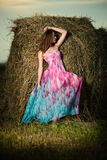 Young Woman Standing In Evening Field Over Haystack. Fashion Sty Stock Images