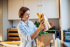 A young woman standing indoors in kitchen, unpacking shopping bag. stock images