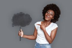 Young woman standing on gray pointing at cloud laughing cheerful stock photography