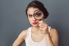 Freestyle. Woman standing isolated on grey with magnifying glass looking camera suspicious close-up royalty free stock images