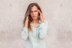 Young woman standing isolated on wall having headache looking camera unhappy stock image