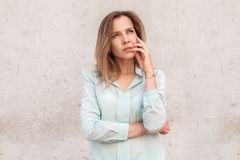Young woman standing isolated on wall looking aside thoughtful stock photography