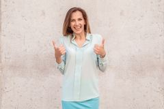 Young woman standing isolated on wall showing thumbs up looking camera cheerful stock photo