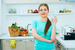 Young woman standing in kitchen with water glass. Royalty Free Stock Photography