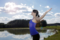 Young woman standing by lake with her arms wide open Royalty Free Stock Photo