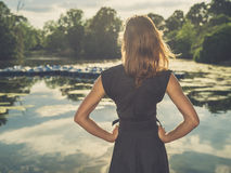 Young woman standing by lake at sunset Royalty Free Stock Image