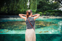 Young woman standing by a large tank of water Royalty Free Stock Photography