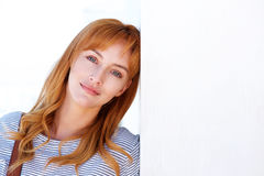 Young woman standing and leaning head on wall. Close up portrait of young woman standing and leaning head on wall Royalty Free Stock Photography