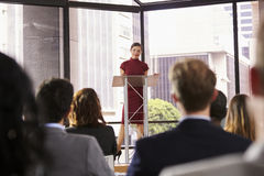 Young woman standing at lectern presenting business seminar Stock Photos