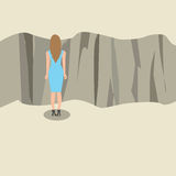 Young woman standing and looking at the edge of a cliff. Stock Image