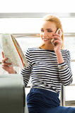 Young woman standing with a map and talking on the phone. Close-up. gathered on a trip Royalty Free Stock Photography