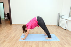 Young woman standing on mat in one of yoga positions Stock Image