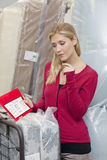 Young woman standing by mattress with price list in furniture store Stock Image