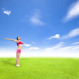 Young woman standing on a meadow with blue sky. Relaxing young woman standing on a meadow with blue sky Stock Image