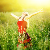 Young woman is standing in meadow enjoying sunlight Royalty Free Stock Photos