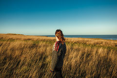 Young woman standing in meadow by the sea Royalty Free Stock Photos