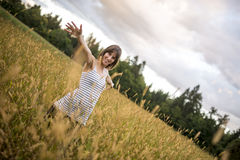 Young woman standing in the middle of autumn meadow with high go Royalty Free Stock Images