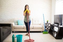 Young woman standing with mop and looking at camera. Young woman wearing casuals and yellow rubber gloves cleaning floor while keeping chin on mop Royalty Free Stock Images