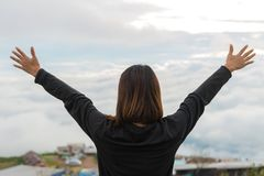 Young woman standing on a mountain with raised hands and looking royalty free stock image