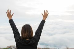 Young woman standing on a mountain with raised hands and looking stock photography