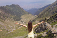 Young woman standing on a mountain top with outstre Stock Photo