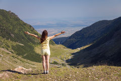 Young woman standing on a mountain top with outstre Stock Images