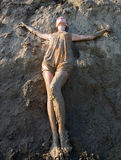 Young woman standing in the mud. In the pose of the cross Royalty Free Stock Images