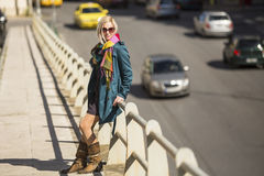 Young woman standing near a busy street. Walk. Stock Image
