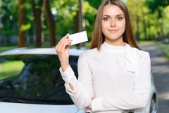 Young woman standing near car and showing card Stock Images