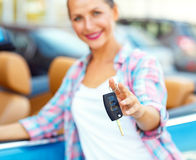 Young woman standing near a convertible with keys in hand Stock Photo