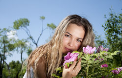 Young woman standing near a dogrose. Portrait of the young woman standing near to a dogrose bush Royalty Free Stock Photography