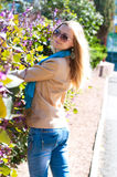 Young woman standing near a flower fence. Young beautiful blonde woman with long hair standing near the fence covered with braiding flowers purple. Woman put on Stock Photography