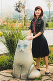 Young woman standing near funny cat statue Royalty Free Stock Photography