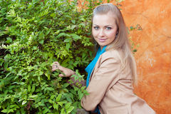 Young woman standing near a green hedge. Portrait of a beautiful young woman. Woman standing near a hedge Royalty Free Stock Photography