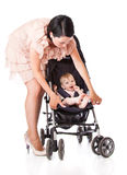 A young woman is standing near her child in a pram. Isolated on a white background Stock Photos