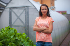 Young woman standing near her greenhouse Stock Image