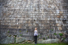 Young woman standing near a huge stone wall. Architecture Royalty Free Stock Photos