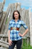 Young woman standing near old wood post fence Royalty Free Stock Images