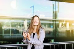 Young woman standing near railway station and chatting by smartphone. Concept of modern technology, fast internet and traveling royalty free stock image