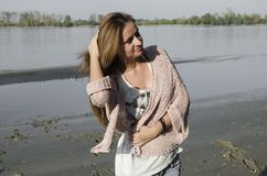 Young Woman Standing near the river. She is standing on sand beach Royalty Free Stock Images